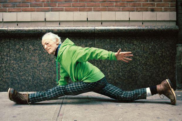 Elderly man doing spilts on street pavement