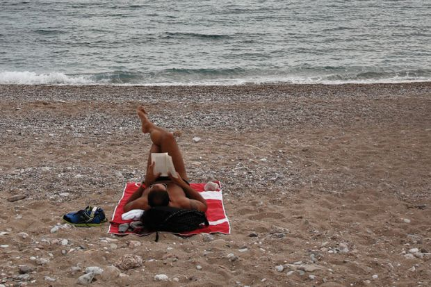 Man lying on beach, Glyfada, Greece
