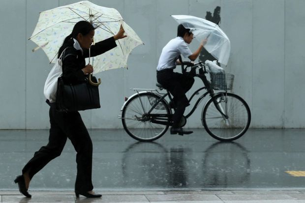Man rides a bicycle ahead of woman walking