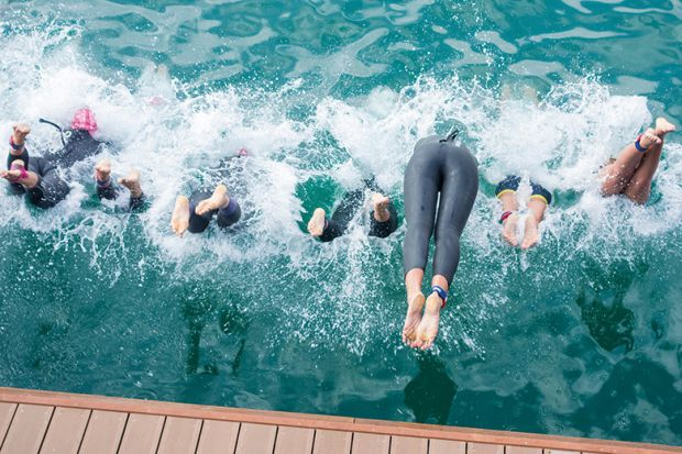 Swimmers diving into water