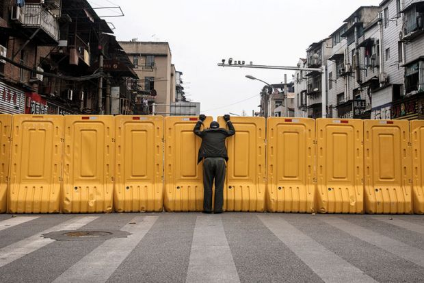 A man wearing a face mask talks to another man through a makeshift barricade wall in Wuhan, Hubei, China as a metaphor for China and Japan to keep borders shut for another term
