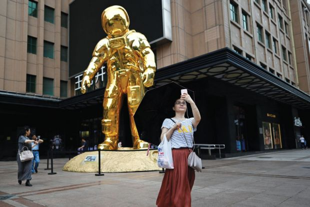 Person taking selfie with an astronaut-installation as a metaphor for  Prioritise women for research funding, Chinese universities told