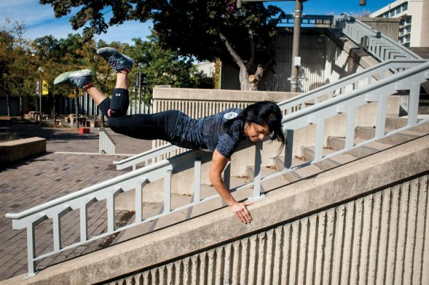 A lady vaults over a stair railing as a metaphor for a quarter of US states 'likely to skip' Biden free college plan
