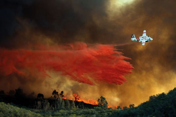 An airplane makes a fire retardant drop on a large hill-top home