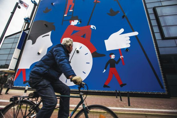 A man rides a bicycle past a wall painting
