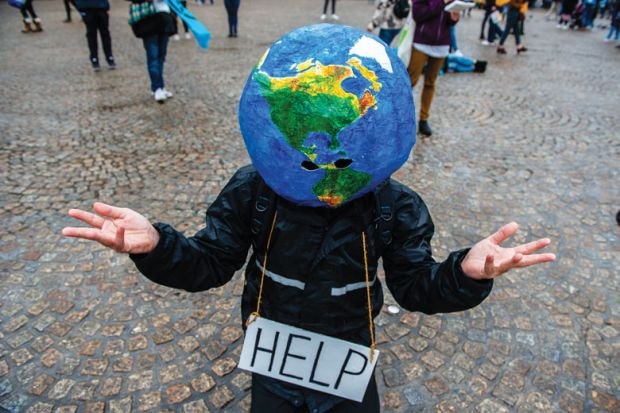 A man with an earth ball on his head and help sign makes hand gesture